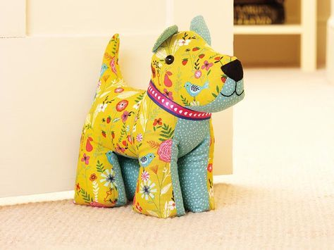 Use leftover fabrics, buttons and ribbons and stitch this cute and colourful dog doorstop make to prop open a door in your house