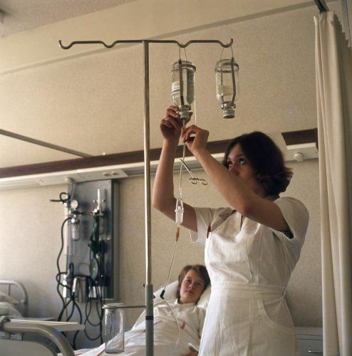 Onbekend | Verpleegster/zuster verwisselt de fles vloeistof van een infuus terwijl de patiënt in het ziekenhuisbed toekijkt, Nederland zonder jaartal.
