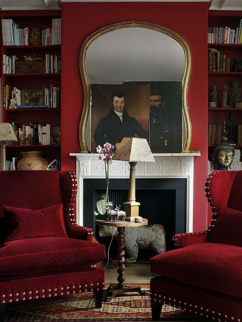 Sumptuous deep red fireplace wall, gold frame mirror, velvet wing back armchairs with brass studding . . . this library-style living room feels very luxurious and part of the Hip Heritage culture . . .