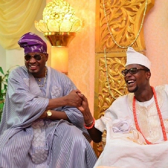 Nigerian Yoruba groom in white Agbada outfit and one of his groomsmen in Grey Agbada outfit