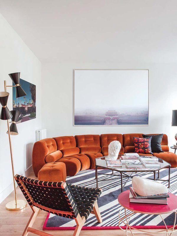 SOFÁ MODULAR Las obras de arte y las piezas con carisma ensalzan el proyecto de reforma de esta vivienda, ideado por las interioristas de Vade Studio. El sofá modular curvo en terciopelo color tabaco, del showroom de María Lladó, rodea la alfombra, de The Rug Company. La butaca de tiras trenzadas es de PLM Design y la mesa de centro octogonal, de Anmoder. En la pared, fotografía de Alejando Guijarro, en YellowKorner.