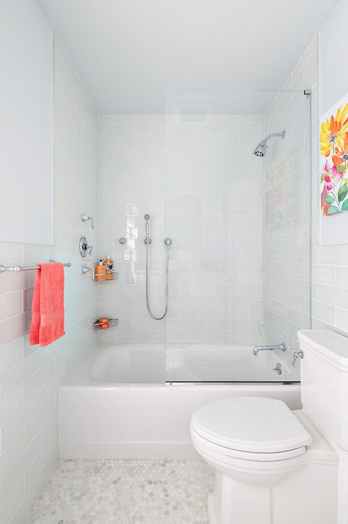 All white subway tile and marble hexagon floors with a glass shower closing. Simple and affordable.