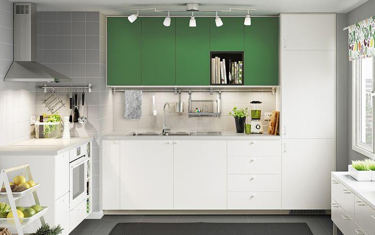 Cucina bianca con ante verdi e piani di lavoro bianchi, cappa in acciaio inossidabile e forno bianco.