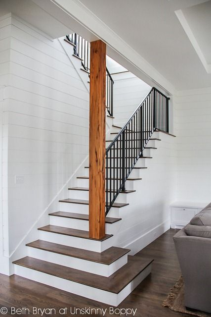 Stairs to the basement -- open staircase Wood planked walls Stained and painted stairs Metal railing
