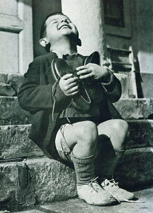 La joie d'un enfant après avoir reçu en cadeau une paire de chaussures pendant la deuxième guerre mondiale. .