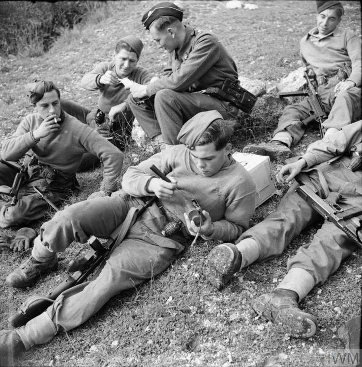 A battle patrol of the 1st East Surreys rest after returning from enemy territory, 16 December 1943. They are armed with Thompson SMGs, grenades and a captured German MP40.