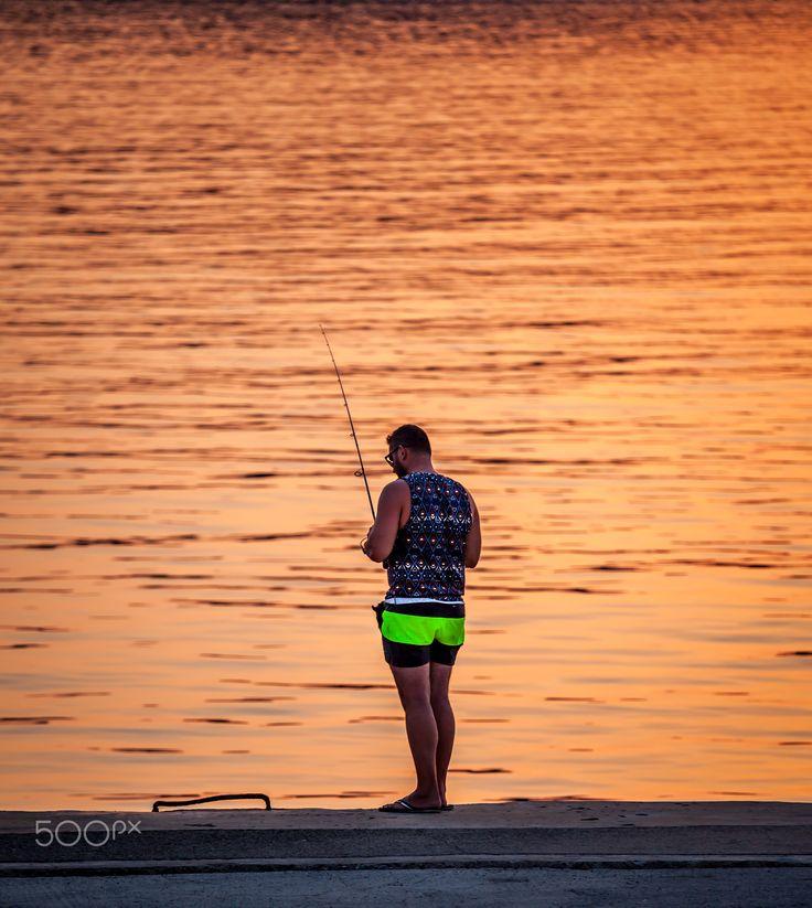 Man Fishing at Sunset - Man fishing alone at sunset in Pilos  Greece