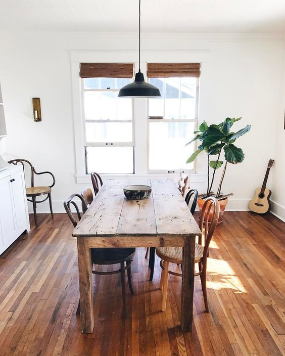 Dining room design idea with blinds, wood table and indoor plant.