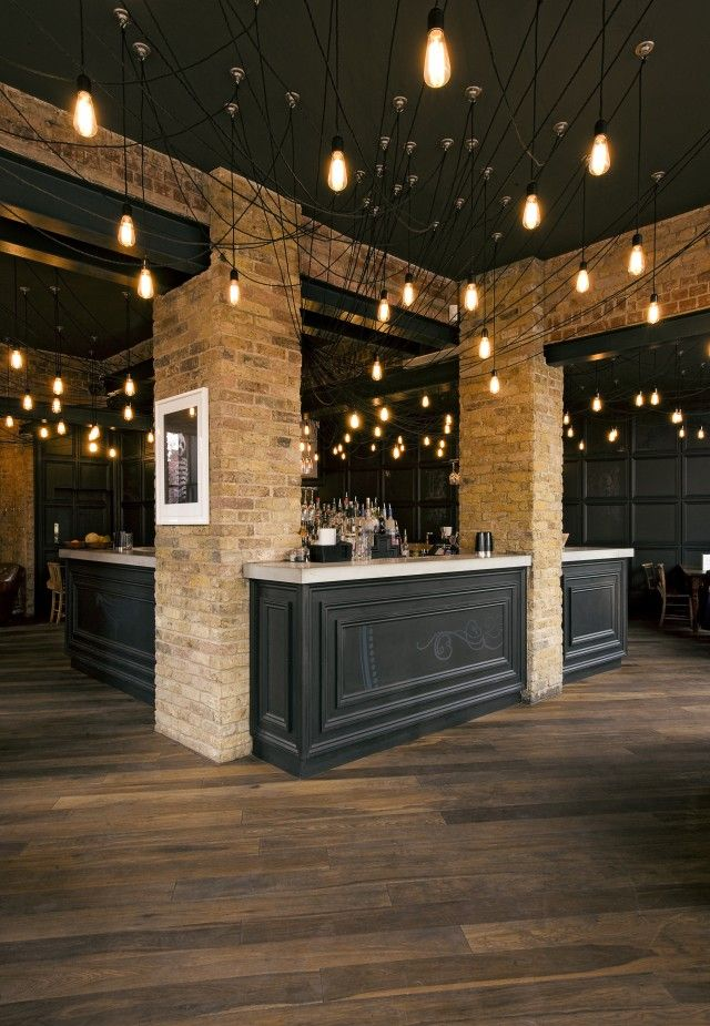 Modern Eclectic: Classic furniture pieces, Herringbone pattern wood flooring, brickstone wall, industrial ceiling. Nice!