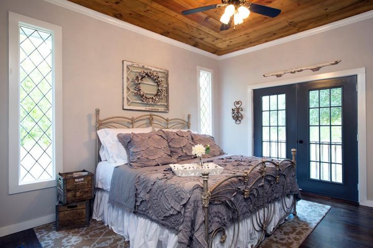 For the Batson's newly remodeled master bedroom, light gray-blue wall paint and white molding offset dark hardwood floors, natural wood ceiling and antique leaded-glass windows that the homeowners discovered at a salvage store.