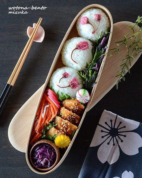 Chicken teriyaki bento box, with sides of saltedcherry blossom onigiri, lemony carrot salad, purple mizuna pickles, and marinated purple cabbage