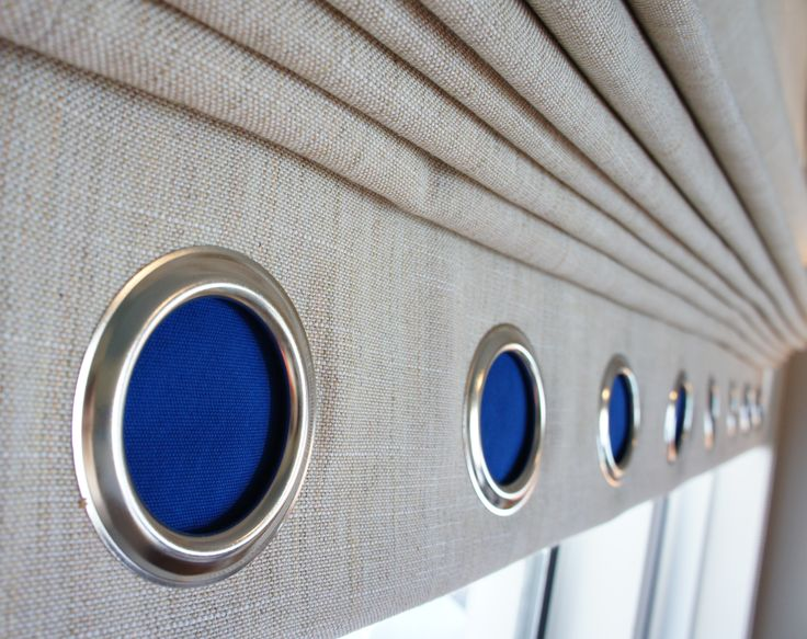 I wanted the large roman shades to remain mostly neutral, but I felt they needed some color and interest. Instead of doing a typical accent color band at the bottom, I chose to use nautical grommets on a reveal band at the bottom. Behind the grommets, I designed a cobalt liner, which created the hint of color I wanted.