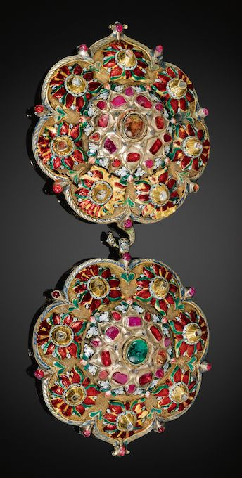 AN OTTOMAN ENAMELLED AND GEM-SET BUCKLE, TURKEY, CIRCA 1700 each of lobed medallion form, the central rosette enamelled with detailed floral motifs and raised gem-set peak comprising lasque and table-cut diamonds, rubies and emeralds, bordered by seven smaller red, green and white enamelled flower-heads with a gem-set tip 9cm. each. diam.