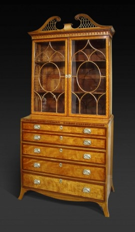 "A George III Satinwood and Satinwood Inlaid Secretaire Bookcase,     Circa 1785,     Height: 95"" Width: 42"" Depth: 22"".       The fretted swans neck pediment over a dentil and lambrequin-molded cornice and curvilinear glazed doors opening to adjustable shelves; the lower section fitted with a secretaire drawer opening to a leather-lined writing surface and arrangements of drawers and pigeon holes, above three crossbanded graduated drawers on splayed feet."