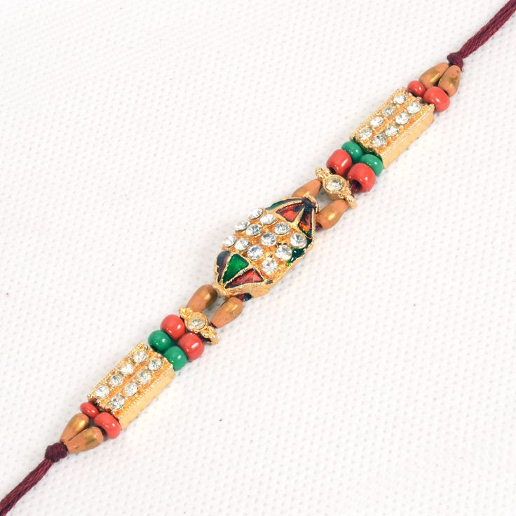 This Rakhi is studded with multiple artificial stones, and beads. The very interesting design of this sacred Rakhi thread available on the online gift store of Giftblooms.com will surely delight your brother in India. Moreover, there are other smaller beads in between - brown, red and green in color, which gives this Rakhi a complete look.