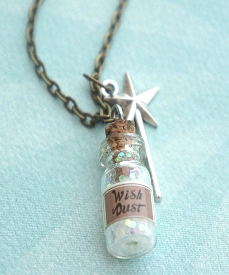 this necklace features a wish dust bottle pendant that measures 2 cm tall. the mini bottle pendant hangs from a bronze chain necklace along with a tibetan silver wand charm. the necklace measures 24 i