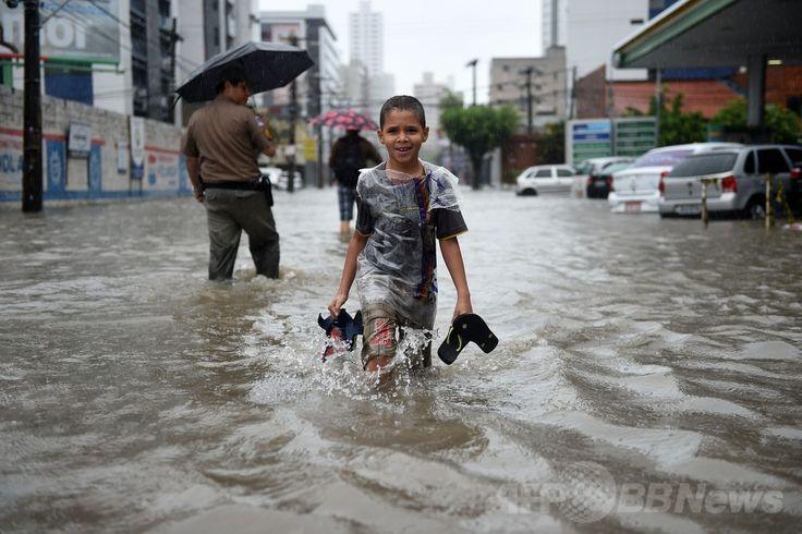 W杯ブラジル大会(2014 World Cup)グループGのドイツ対米国の試合が行われたブラジル北東部レシフェ(Recife)で、豪雨のため冠水した道路を歩く人々(2014年6月26日撮影)。(c)AFP/PATRIK STOLLARZ ▼27Jun2014AFP|ブラジル・レシフェで豪雨による洪水、W杯ドイツ対米国戦の直前 http://www.afpbb.com/articles/-/3018976 #Recife #Flood