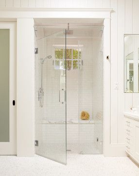 Large white tile shower with bench, steam shower, and window for natural light traditional bathroom
