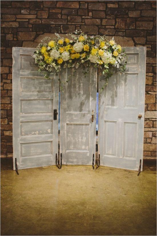 doors with yellow floral arrangement as a ceremony backdrop #ceremonybackdrop #weddingceremony #weddingchicks http://www.weddingchicks.com/2014/01/17/gray-and-yellow-wedding-2/