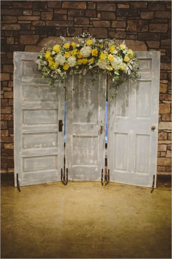 doors with yellow floral arrangement as a ceremony backdrop #ceremonybackdrop #weddingceremony #weddingchicks http://www.weddingchicks.com/2014/01/17/gray-and-yellow-wedding-2/