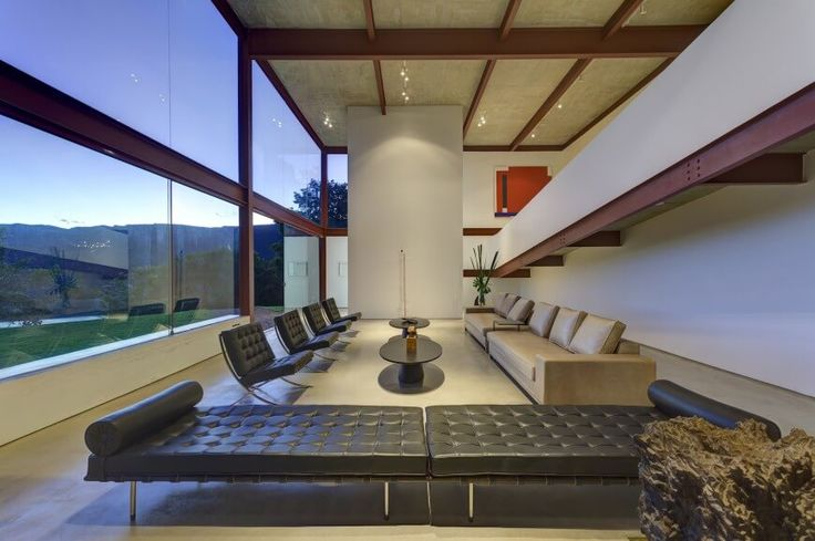 A catwalk ramp overlooks the sprawling, artfully appointed living room. A set of button tufted black leather chairs faces a pair of lengthy contemporary brown sofas, while a pair of chaise lounges in the foreground define the edge.