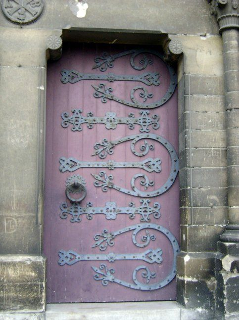 Ornate ironwork on a beautifully hued door.