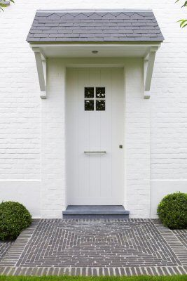 All-white entrance to a white brick home