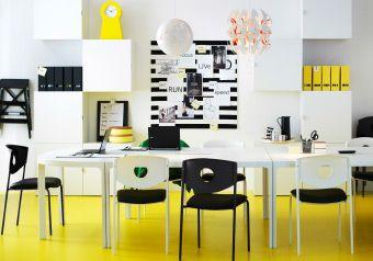 Et farvestrålende kontor med gult gulv, hvide vægskabe og 3 BEKANT skriveborde sat sammen til et konferencebord.