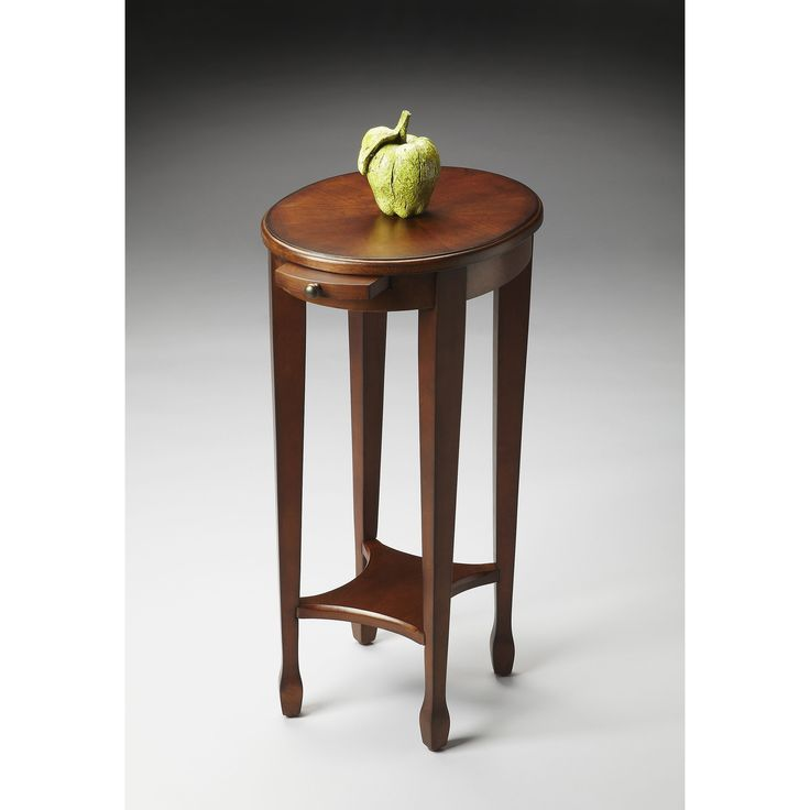 This round chestnut accent table perfect accent for your favorite living room chair. It's durably constructed of poplar wood solids, wood products, and veneers and features a handy pullout shelf that's perfect for setting down a drink or remote.