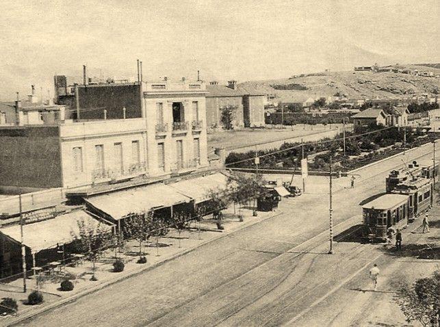 Καλλιθέα 1920: Θησέως και Χαροκόπου με το τραμ. Το τριώροφο γωνιακό νεοκλασσικό (υπάρχει ακόμη) και η Χαροκόπειος.  Στο βάθος αδόμητη η απόληξη του λόφου Φιλοπάππου, τα σημερινά Άνω Πετράλωνα.