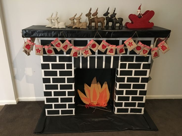 Fake fireplace made from cardboard and black paper rectangles glued on with a painted mantel.