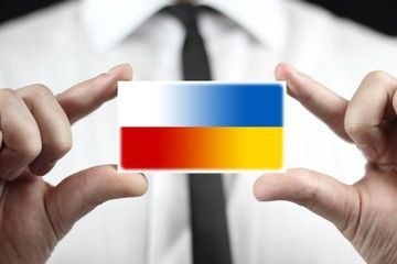 Businessman holding a business card with Poland and Ukraine Flag