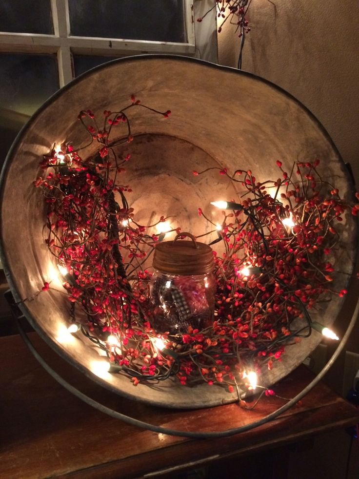 Don't throw out your old buckets. This aged beauty had rusted through on the bottom which made the perfect place to string some lights through. A simple, easy primitive look.
