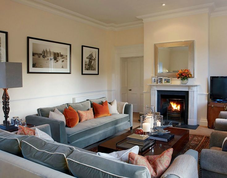 Gray sofa orange accents white mantel fireplace comfy for Grey orange living room