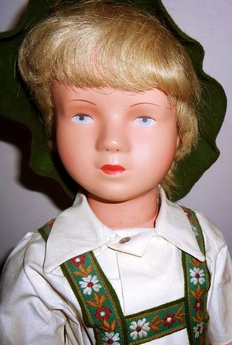 """16"""" celluloid boy doll in factory original clothes, with blond human hair wig and painted eyes, wearing a traditional German lederhosen (casual boys' leather breeches), designed by Käthe Kruse, West Germany, 1950-55, by Schildkröt."""