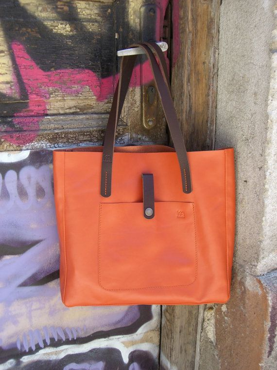 The handmade tote is made of high quality Italian leather in orange color, one external pocket with a tic tac.  You can hold your books, laptop, tablet and other items.  The shoulder straps are made from 100% genuine leather in a brown color.   The approximate size of the bag is:  Height: 30 cm (11.8 in.) Width: 33cm (13 in.) Depth: 6cm (2.6 in.)  If you have any personal preferences, send us a message and we will do our best to work something out for you.  Thanks for visiting