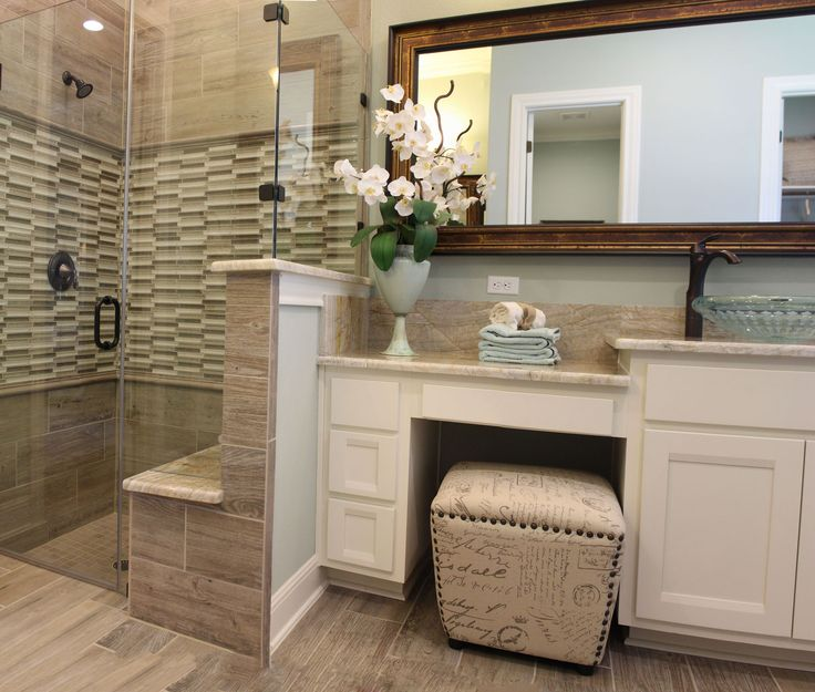 Master bath with white cabinets with knee space, vanity seat and shower with built in bench seat. Cabinets in Camley style by Burrows Cabinets