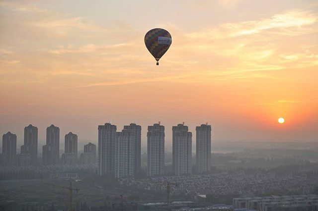 A hot air balloon flies over residential buildings in Wuqing District of Tianjin, China July 11, 2017. Picture taken July 11, 2017. REUTERS/Stringer #China #Asia