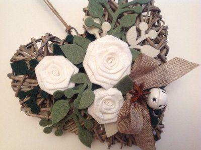 Cuore di vimini con rose di lino bianco e rametti di feltro verdi