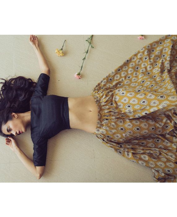 This ochre and black lehenga set contains a lehenga skirt and blouse. The skirt is crafted from pure cotton that has been hand block printed in