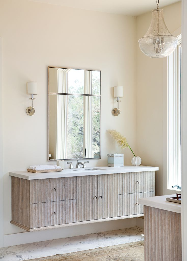 Cream-colored bathroom with Jamie Young Nimbus Chandelier