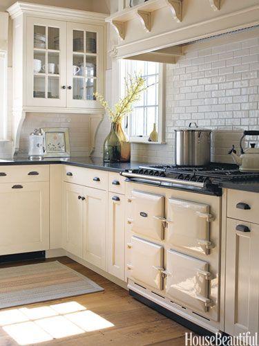 So warm and lovely! Creamy cabinets and a grayish-white subway tile backsplash. Warm hardwoods... So pretty.