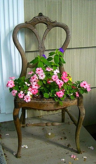 Dining room chair with the seat removed and planted with flowers