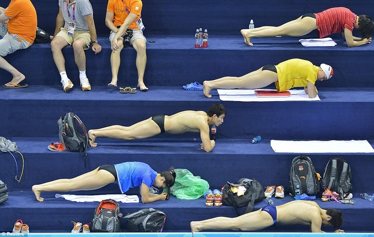 Chinese swimmers perform strength exercises at the Aquatics Centre as part of a training session ahead of the Olympic Games