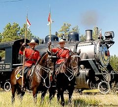 Vintage train locomotive 1077 gets an RCMP escort near the Fort Steele Heritage Townsite grounds.