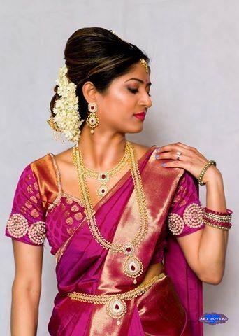 South Indian bride. Gold Indian bridal jewelry.Temple jewelry. Jhumkis. Pink silk kanchipuram sari.Bun with fresh jasmine flowers. Tamil bride. Telugu bride. Kannada bride. Hindu bride. Malayalee bride.Kerala bride.South Indian wedding.