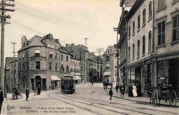 En 1907, le tramway sur le trident des rues Couillard, Garneau et côte de la Fabrique. On remarque à gauche la Maison Livernois, studio de photographie réputé de Québec, et à droite, au tournant de la rue, la boutique de l'horloger Cyrille Duquet suivie de la librairie J. P. Garneau. BAnQ, Centre d'archives de Québec Collection Magella Bureau