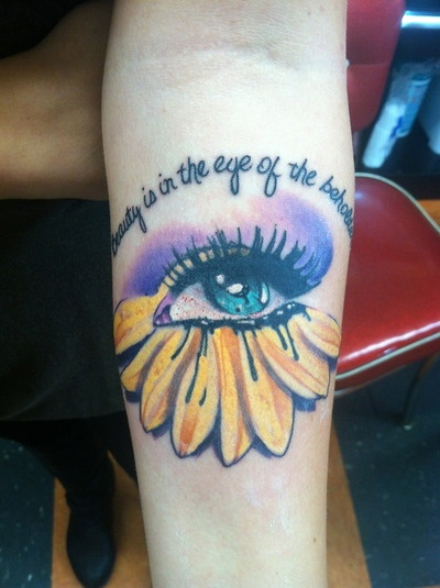 "Done by Paul @ Tip Top Tattoo in Ft. Wayne, IN. Thought up the idea to incorporate a sunflower and an eye with the quote that says ""Beauty is in the eye of the beholder."" I'm a hairstylist and I love to make people look & feel beautiful."