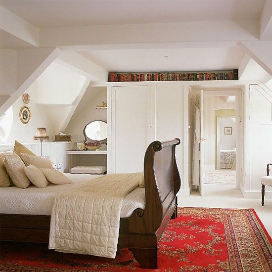 Loft bedroom  White walls and cream carpet give this loft space a light and fresh appearance. Built-in wardrobes follow the dimensions of the exposed roof beams and blend into the scheme, while the walnut sleigh bed and red Persian rug add colour and depth.
