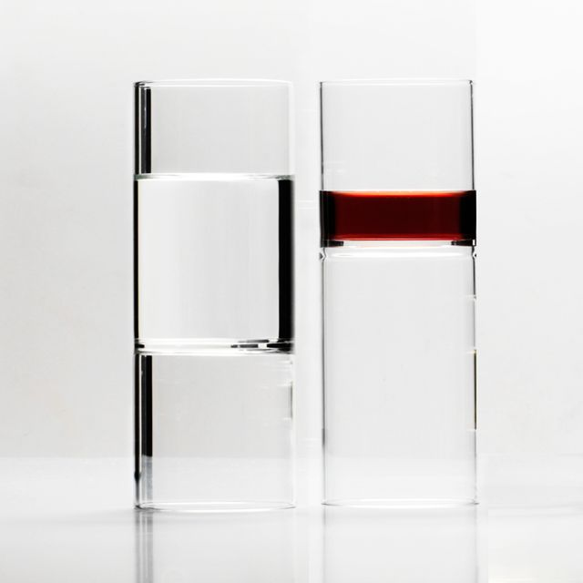 """the Revolution Wine and Water Glass is created from a pure extrusion of hand-blown glass, combining two glasses into one. When in use, its contents appear to float, seeming to defy gravity. This distinctive design allows for flexibility in function holding water, wine, champagne or any other liquid. """